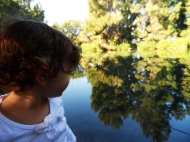 toddler sitting by lake